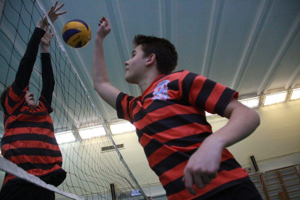 Ученики школы № 2097 Аркадий Мекрылов и Алексей Гусев (справа налево) разминаются перед стартовым матчем соревнований по волейболу «Серебряный мяч». Фото: Павел Волков