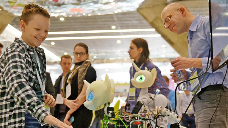 Участник выставки Skolkovo Robotics 2019 Олег Гончаров (справа) демонстрирует юному посетителю технопарка Роману Морозову свой проект — модульного программируемого робота «Свити бот» .Александр Кожохин,