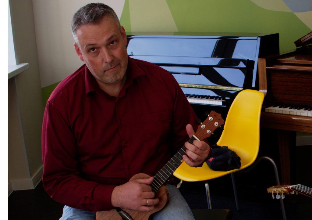 Композитор, гитарист и педагог Алексей Орочко показывает, как правильно играть на небольшой гавайской гитаре, которую называют укулеле / Даниил Данченко, «Вечерняя Москва»
