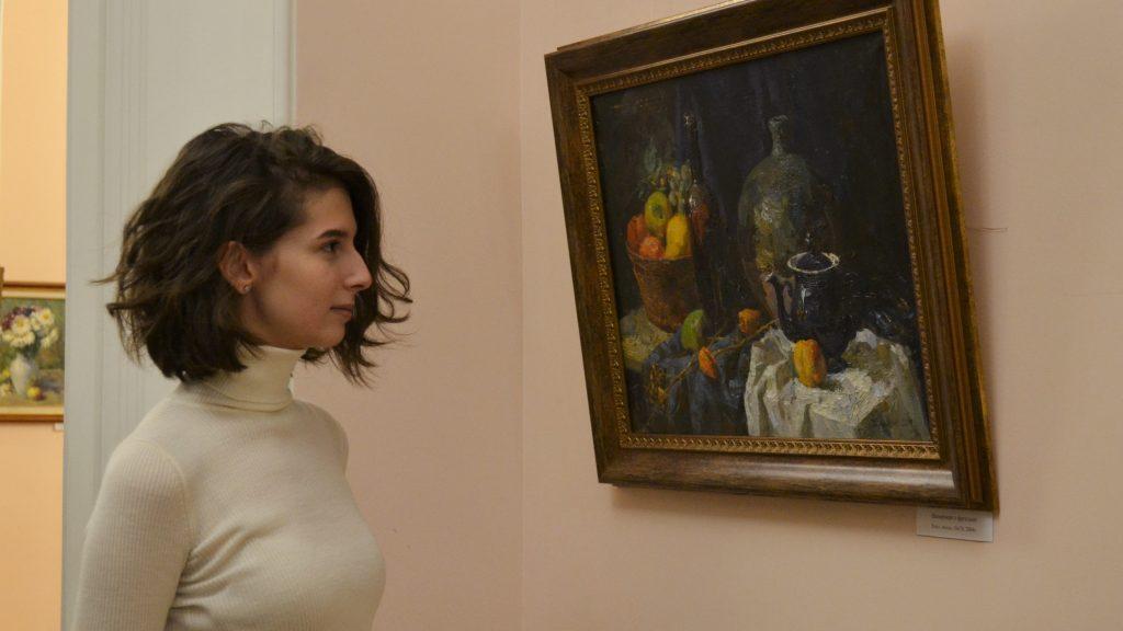 Посетитель выставки Яна Костюк рассматривает работы Олега Карасева, среди которых и «Приближение весны» , ФОТО: Анна Коханова