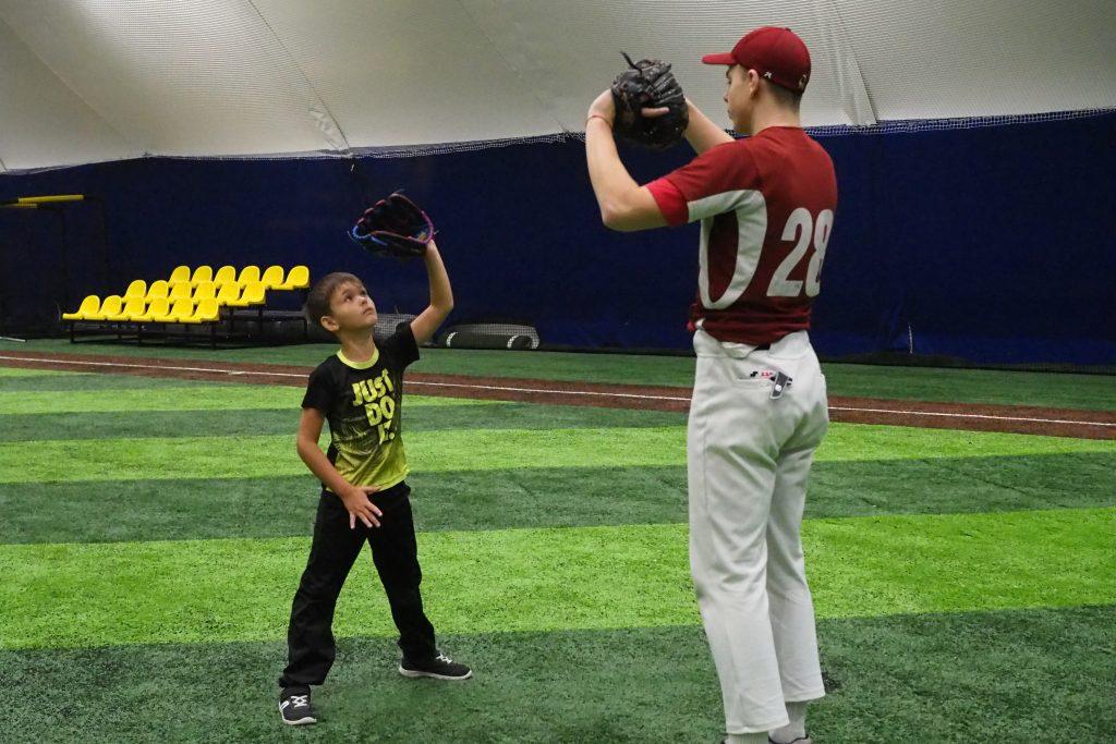 Тренер бейсбольного клуба «Олимпия» Никита Монахов показывает пришедшему посмотреть на тренировку Косте Бугрову, как правильно ловить бейсбольный мяч в перчатку, ФОТО: Элина Масимова