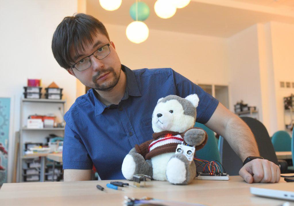 Преподаватель школы № 1354 «Вектор» Василий Кропачев вместе со своей разработкой. Пока робот «живет» в оболочке обычной мягкой игрушки, но совсем скоро обретет уникальную внешность