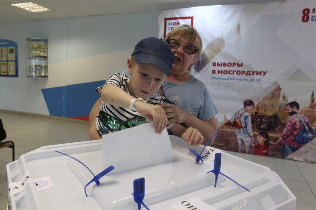 Галина Захоревич проголосовала на выборах. Ее внук Тимофей Барыкин опускает бюллетень в специальную урну
